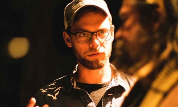 Tyler Savage on set, wearing an unbuttoned grey shirt over a t-shirt, a baseball cap, and glasses. He is studying the actor standing in front of him out of focus, both are washed in an orange light against a dark background.